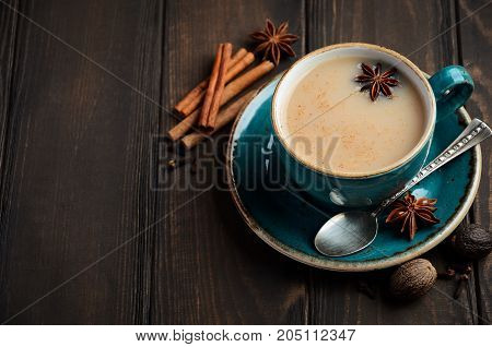 Indian masala chai tea. Spiced tea with milk on dark  wooden background, selective focus, copy space.