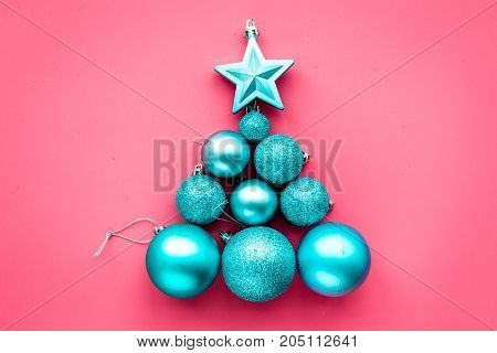 Christmas toys in shape of christmas tree. Blue balls and stars on pink background top view.