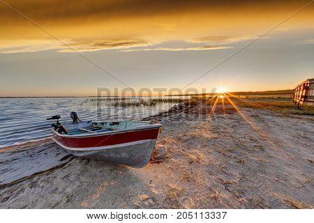 Boat On Beach At Sunrise Over Buffalo Lake, Alberta