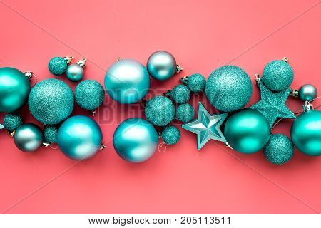 Christmas toys. Blue balls and stars on pink background top view.