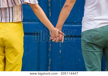 Close up of young modern couple holding hands in front of blue retro door. Love and relationship concepts.