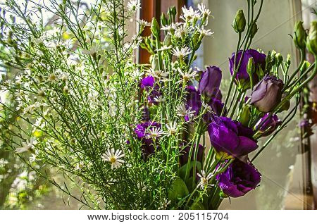 Purple flowers Lisianthus and branches delicate white wildflowers on the windowsill on a bright sunny day