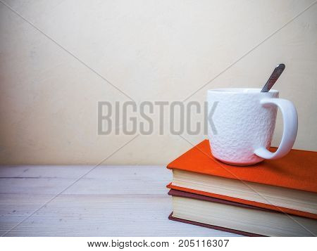 View on the pile of books and cup of tea lying on the wooden table