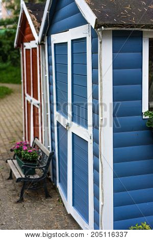 two small red and blue house with wood boards and flower bouquet scandinavian style garden house cute