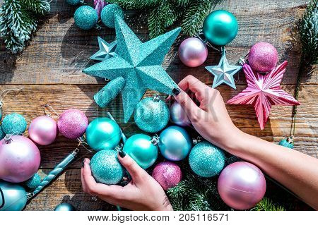 Decorate the christmas tree. Hands hold xmas toys. Stars and balls near pine branches on wooden background top view.