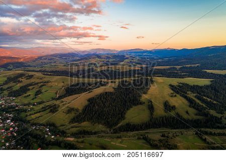 Beautiful nature landscape aerial view of the village in the Carpathian mountains against a beautiful sunset sky