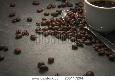 A coffee cup with a spoon and some coffee beans on a gray background