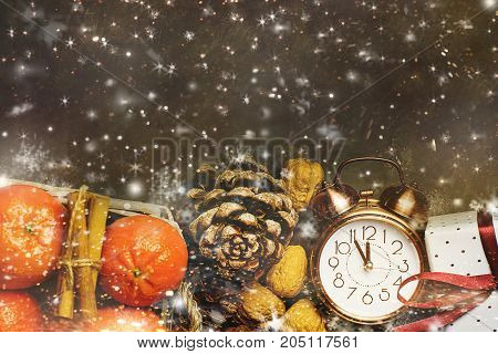 Christmas New Year Greeting Card Tangerines in Wicker Basket Vintage Alarm Clock Five Minutes to Midnight Pine Cones Gift Box Walnuts. Dark Background Snow Flakes Golden Glitter Magical. Copy Space