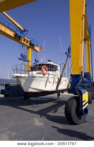 boat yellow crane travelift lifting motorboat for yearly antifouling hull treatment