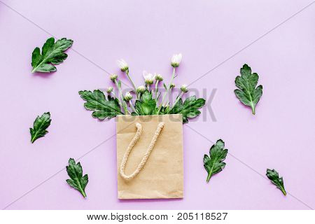 Floral pattern. Bouquet in a paper bag on purple background top view.