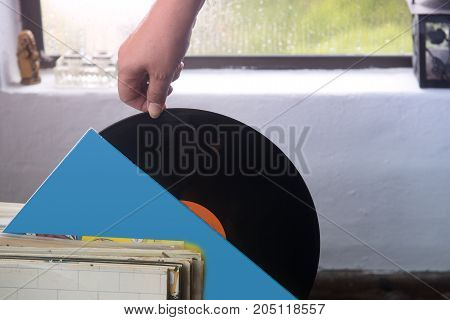 The girl's hand pulling the vinyl plate out of the envelope