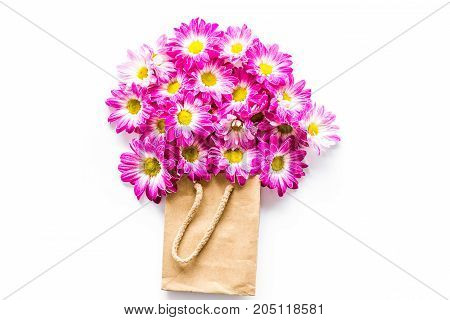 Floral pattern. Bouquet in a paper bag on white background top view.