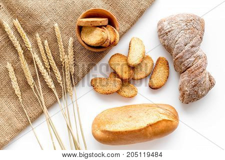 fresh tasty bread with wheat flour in bakery shop on white desk background top view