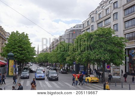 Paris; France- May 01; 2017: People are walking along the Champs Elysees and Georges V Avenue. On the avenue the car is moving