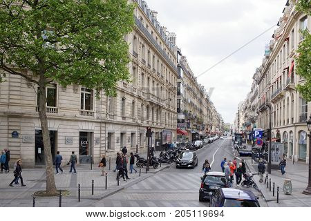 Paris; France- May 01; 2017: Champs-Elysees and the street Pierre Sharon are people. Along the street are cars moving