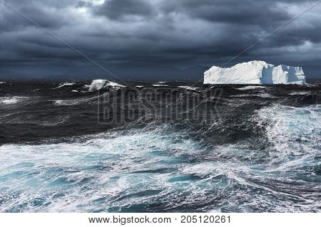 Big Iceberg Drifting in Dark Stormy Ocean