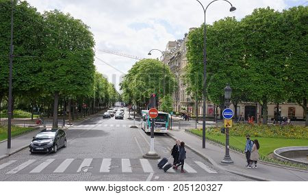Paris; France- May 01; 2017: People walk along the Champs Elysees and Franklin Delano Ruzvelt Avenue. On the avenue the car is moving