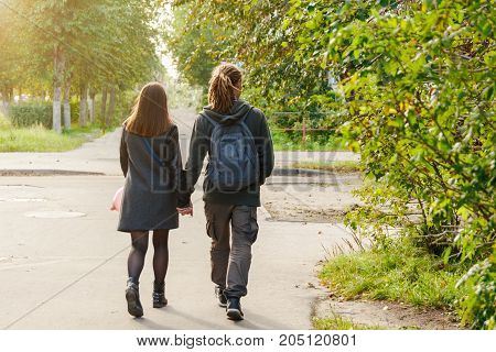 couple in love walking down the street holding hands