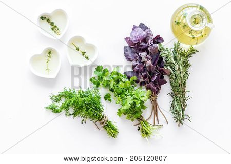 home cooking with fresh greenery and organic oil on white kitchen table background top view