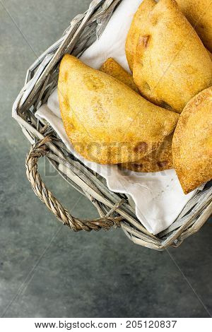 Homemade freshly baked Empanadas Turnover Pies with pisto vegetable cheese filling in tomato sauce in wicker basket. Spanish pastry. Dark concrete stone background. Top View Minimalist. Copy Space.