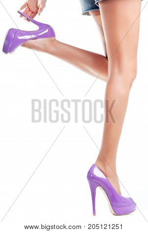 A girl in purple high-heeled shoes holds on to one heel.