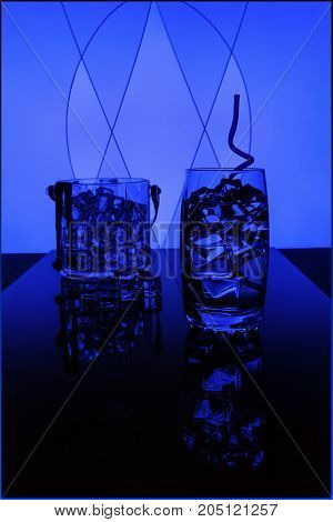 glass with water with ice cubes on a blue background