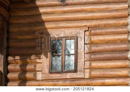 A window in a wooden wall with the reflection of sunlight