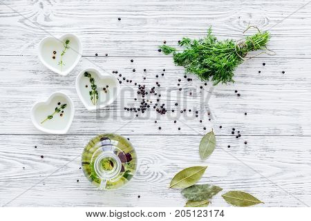 natural oil and fresh greenery for restaurant cooking with spices on wooden kitchen table background top view