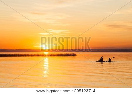 Silhouette Of Two Canoeists On Lake During Sunset