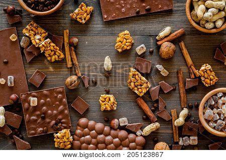 Preparing chocolate. Chocolate bars, nuts, cinnamon on dark wooden background top view.