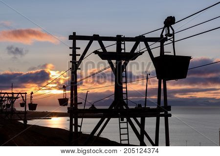 Silhouette of the old cableway for transporting coal from mines in Longyearbyen Svalbard. Midnight sun scenery with light clouds and mountains in background.
