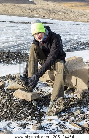 Teenager attaching ice spikes to his shoes to walk on glacier. Longear glacier in Svalbard in background.