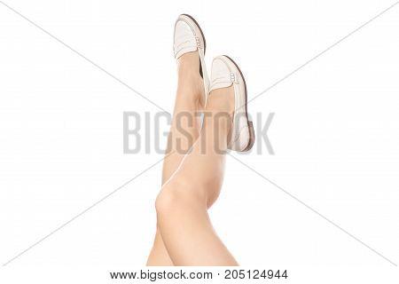 Female legs white shoes on white background isolation