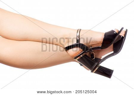 Female legs feet black sandals shoes isolated on white background isolation