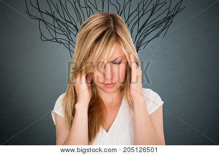 Close-up Of Stressed Young Woman Against Gray Background