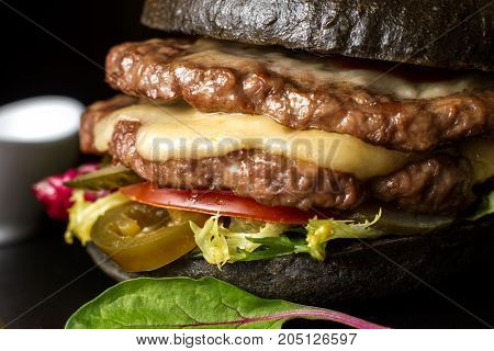 Black double hamburger made from beef, with jalapeno pepper. Cheese beautifully flows from the burger. Big close up.