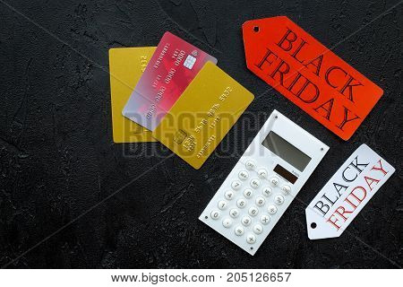 Words black friday on colored labels near bank cards and calculator on black background top view.