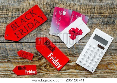 Words black friday on colored labels near bank cards and calculator on wooden background top view.
