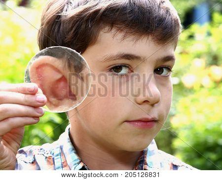 Teen Boy Magnify  His Ear With Lense