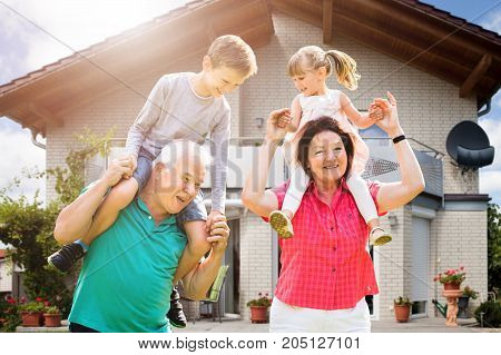 Smiling Grandchildren's Sitting On Grandparent's Shoulder Enjoying Outside Their House