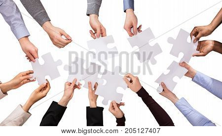 Elevated View Of Hands Holding White Jigsaw Puzzles Against White Background