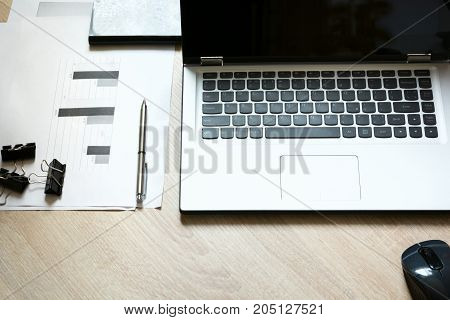 Corporate identity mock up on desk with laptop and documentation with graphics.