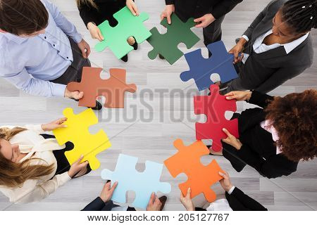 Group Of Business People Standing In Circle Holding Colorful Jigsaw Puzzles In Office