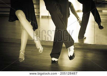 Couple of dancers dancing lindy hop in bright gold and black and white shoes
