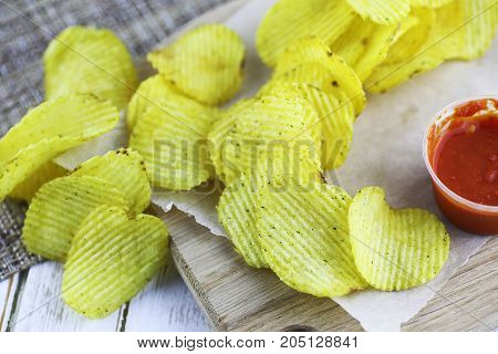 Potato chips on a wooden tray on a white table