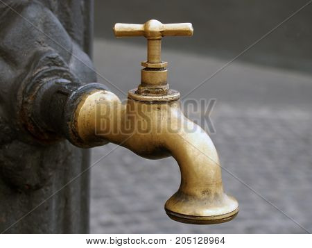 old vintage brass tap outdoors on iron post