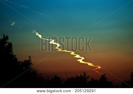 Trail smoke of a fallen asteroid meteor at after sunset in the forest