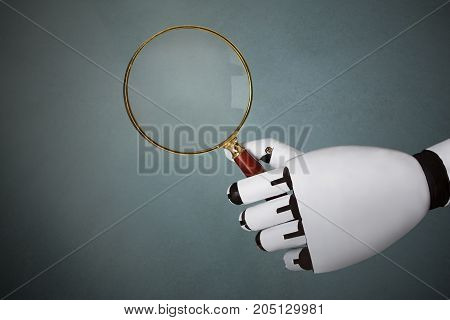 Close-up Of Robot's Hand Holding Magnifying Glass