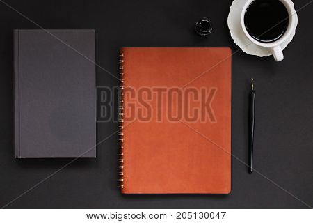 Dark masculine styled desk top with coffee, book, pen and ink and leather planner.