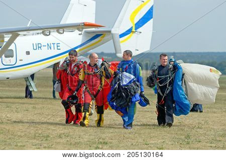 Kharkiv Ukraine - August 26 2017: Skydiver carries a parachute after landing at the airfield Korotych Kharkov region Ukraine on August 26 2017